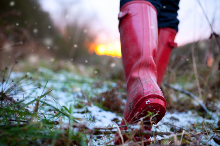 Low angle shot of red wellied feet walking over snow covered ground with snow falling and glowing sunset beyond. Shallow depth of field with focus on heel of boot.