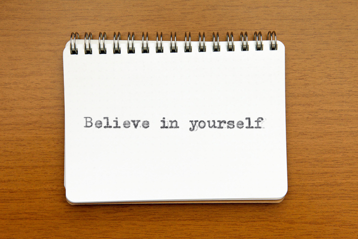 Believe in yourself: motivational quote typewritten on a notepad opened on a wooden desk. Positive thinking, incentives, self confidence and inspiration for life.